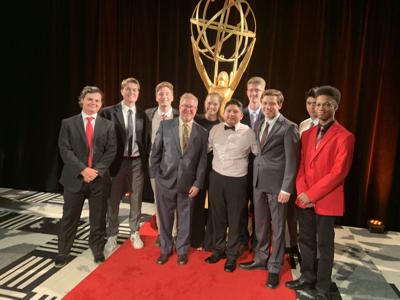 Alpharetta High School Students smile in front of the Emmy Statue