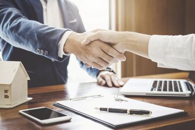Real estate agent and customers shaking hands