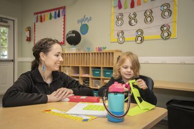 Oak Grove Academy teacher guides student during arts & crafts activity