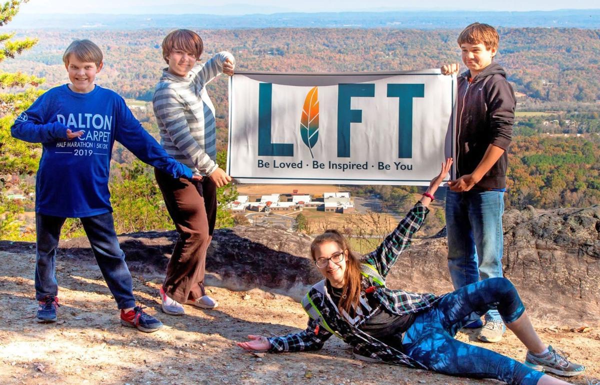 LIFT kids holding sign