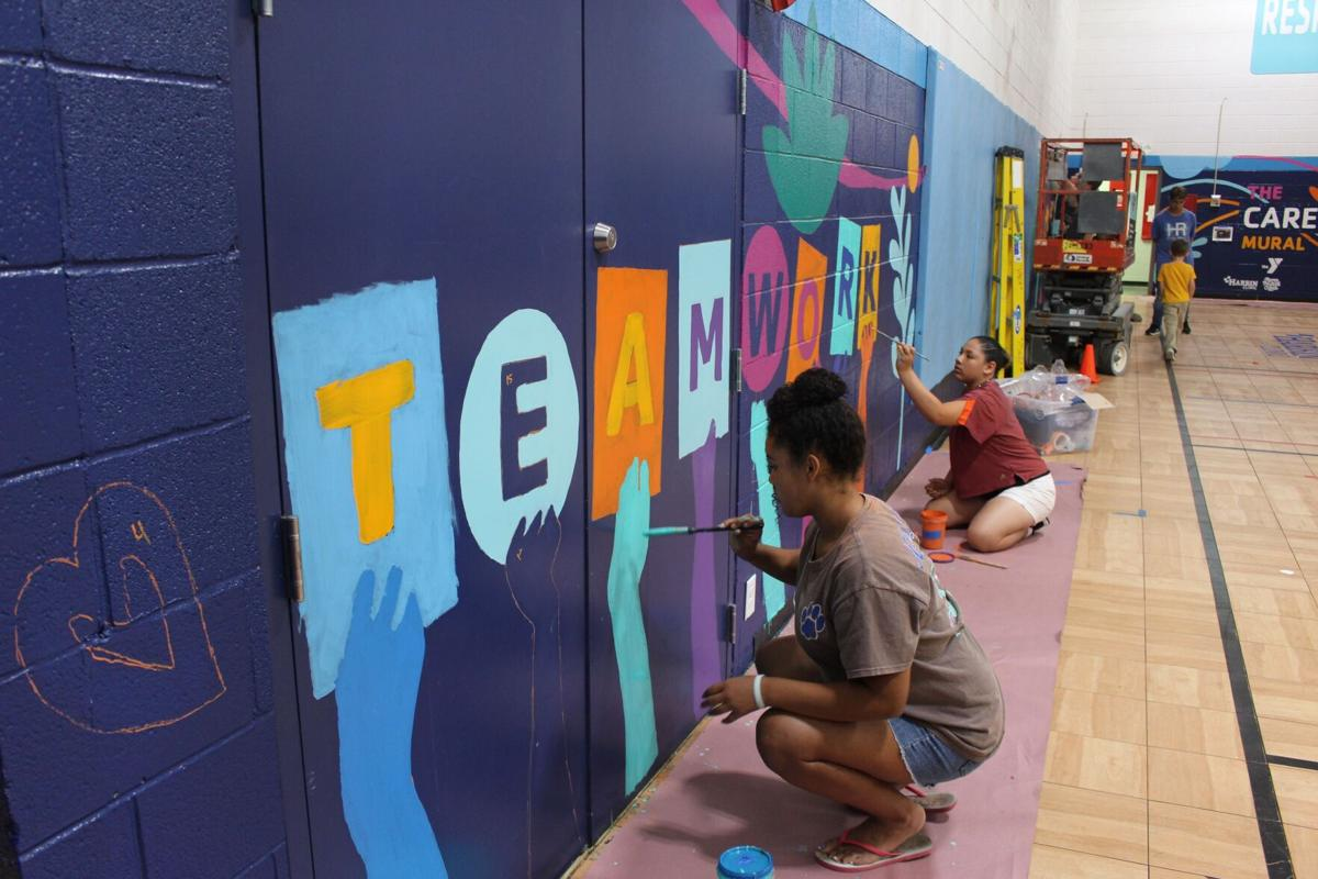 Community volunteers come together to work on Care Mural at YMCA