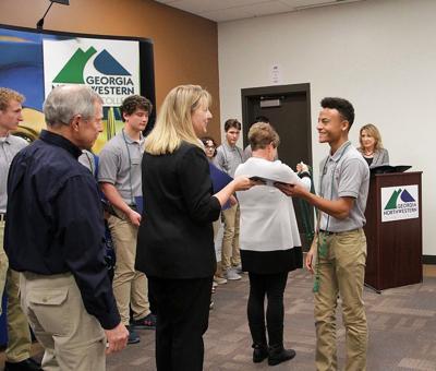 Malik Ware receiving certificate from GA Northwestern president Heidi Popham