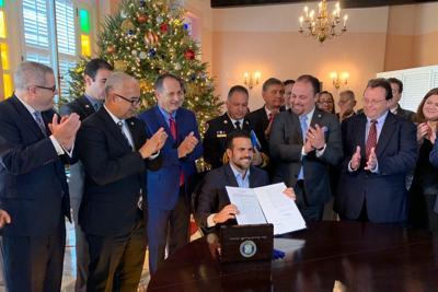 El gobernador Ricardo Rosselló firma la orden ejecutiva.