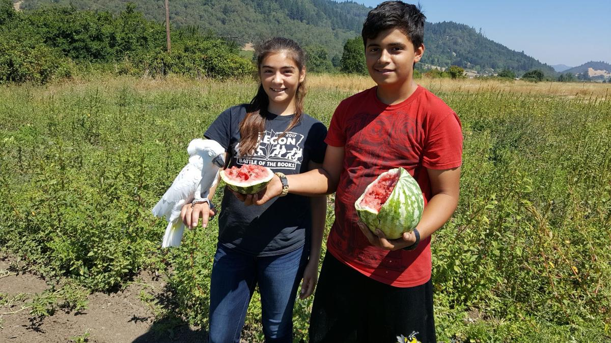 Mariyah and Buddy Valadez with melons
