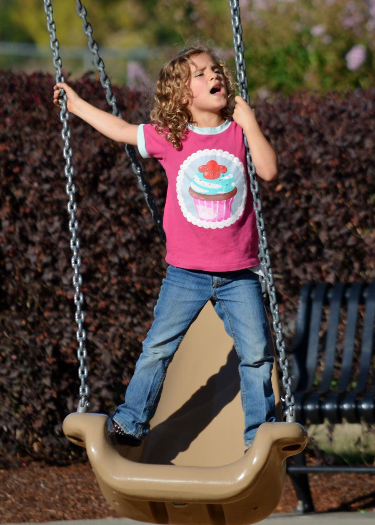 Willow Weldon of Roseburg, 6, yells for her dad, Lee, to push her on the swing at the Stewart Park playground on Tuesday. Weather forecasts are calling for temperatures in the low 90s, which is unseasonably warm for late September.