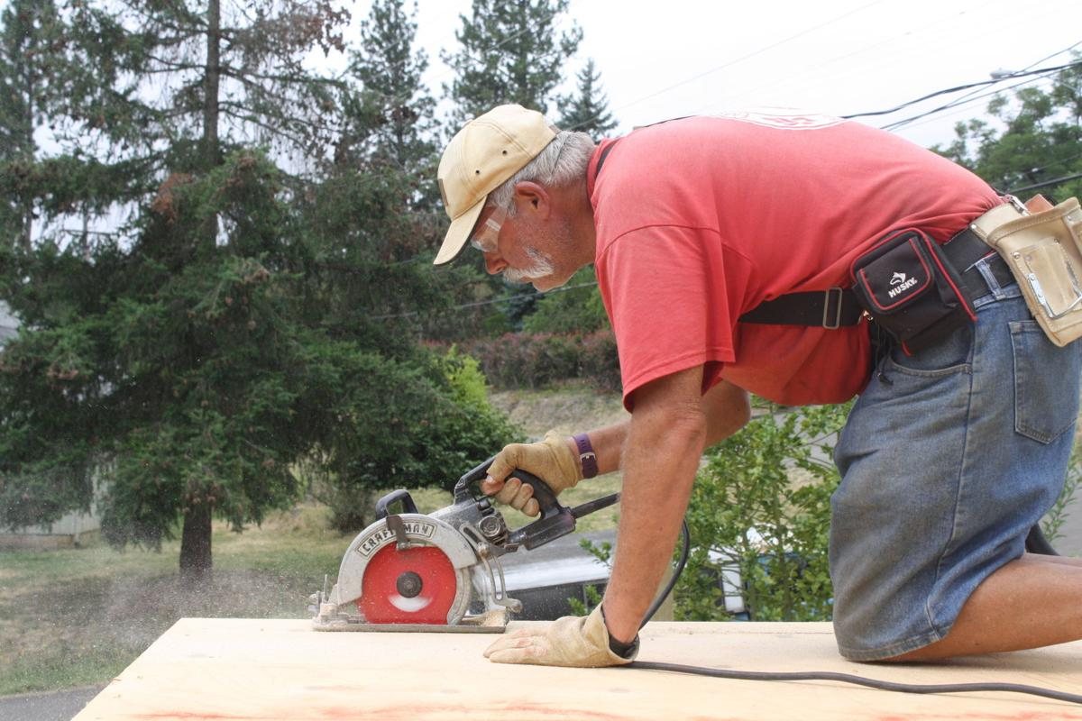Andrew Austin trims plywood during construction