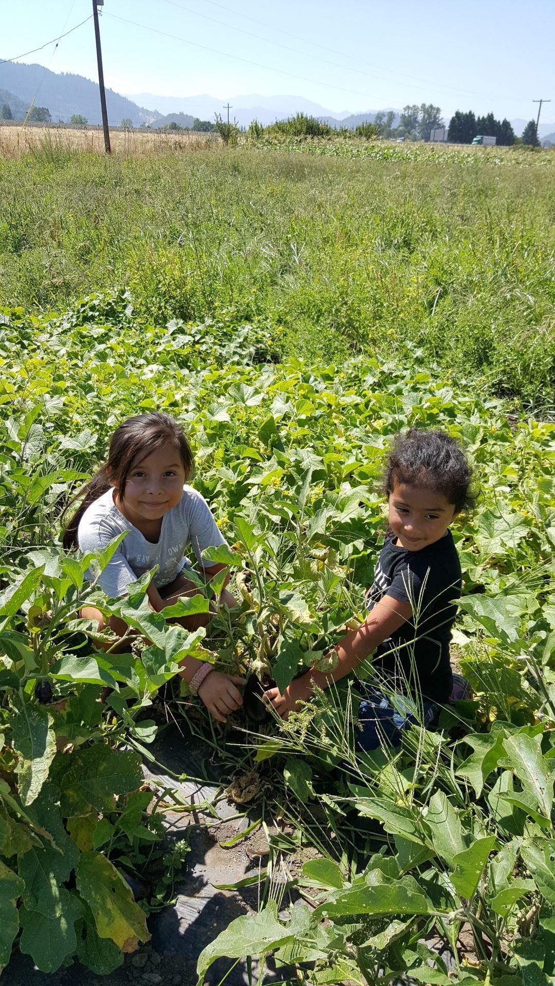 Katalina and Mayte Valadez showing off an eggplant