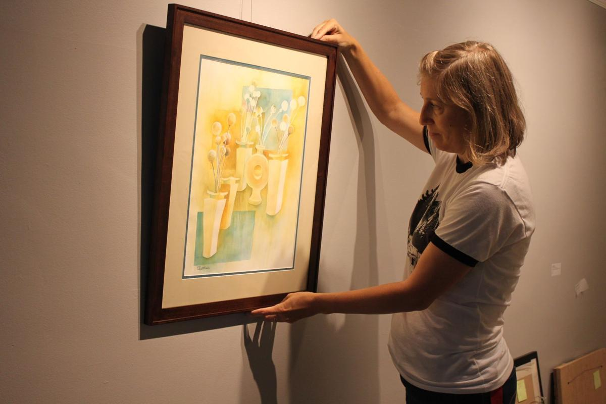 UVAA gallery manager hangs picture for member art show