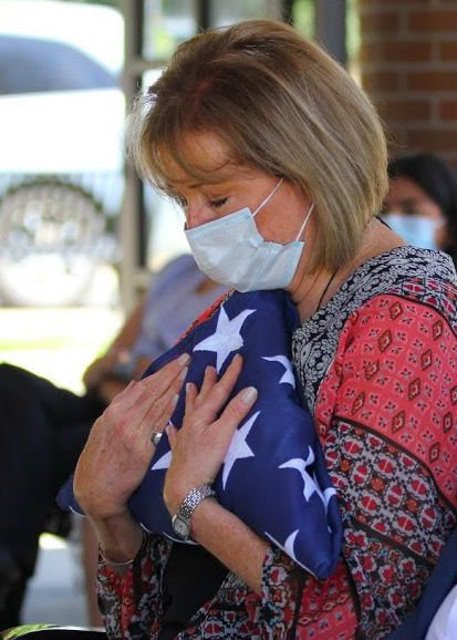 Sharon Berube clutches the American flag in honor of her father