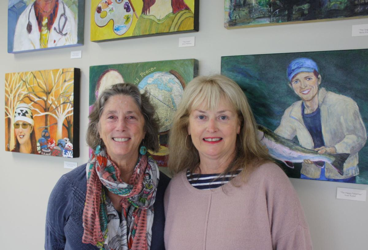 Marjorie Feldman and Janice Matthews stand in front of one of their art displays