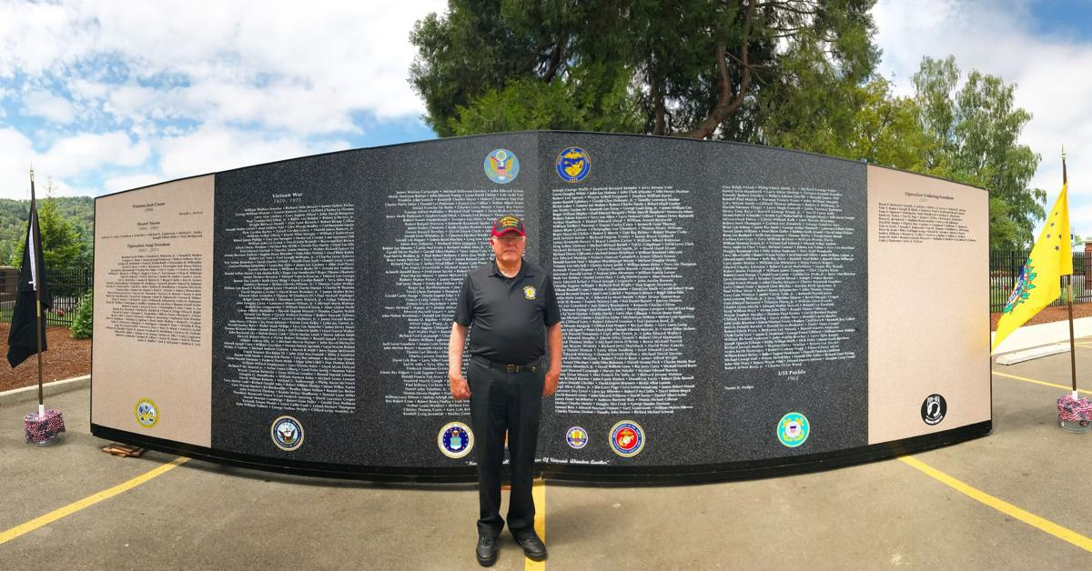 Vietnam helicopter pilot  Tom Davis in front of traveling Vietnam wall