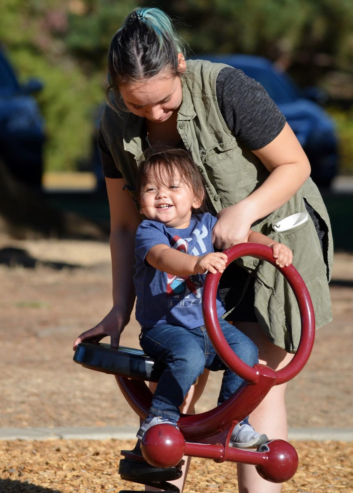 Danielle Stevens of Roseburg, top, pushes her 1 1/2-year-old son, Dominic, Tuesday afternoon at Stewart Park in Roseburg. Weather forecasts in Douglas County are calling for high temperatures in the low 90s, and unseasonably warm temp for late September.