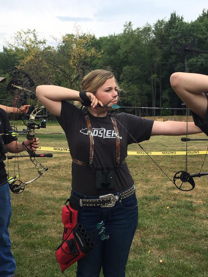 Lila Ferguson sighting in her archery equipment