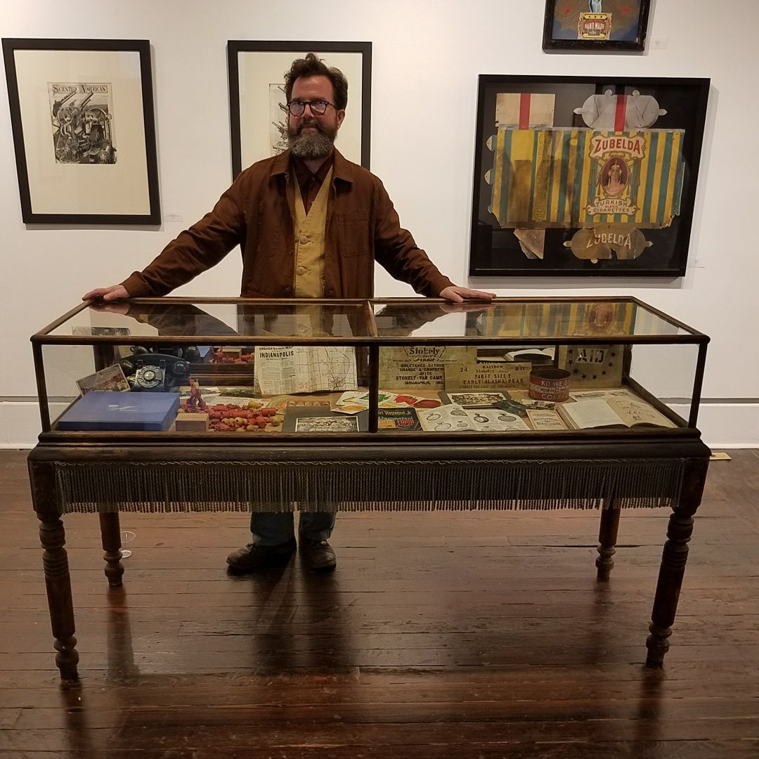 Kipp Normand with a display case in his exhibition 'Historicity'