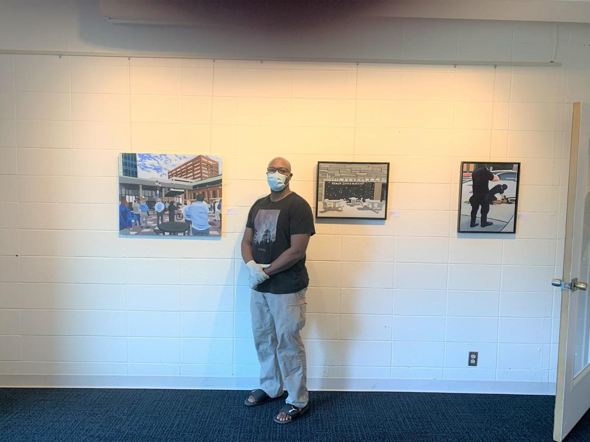 Courtland Blade in front of his paintings at the Harrison Center