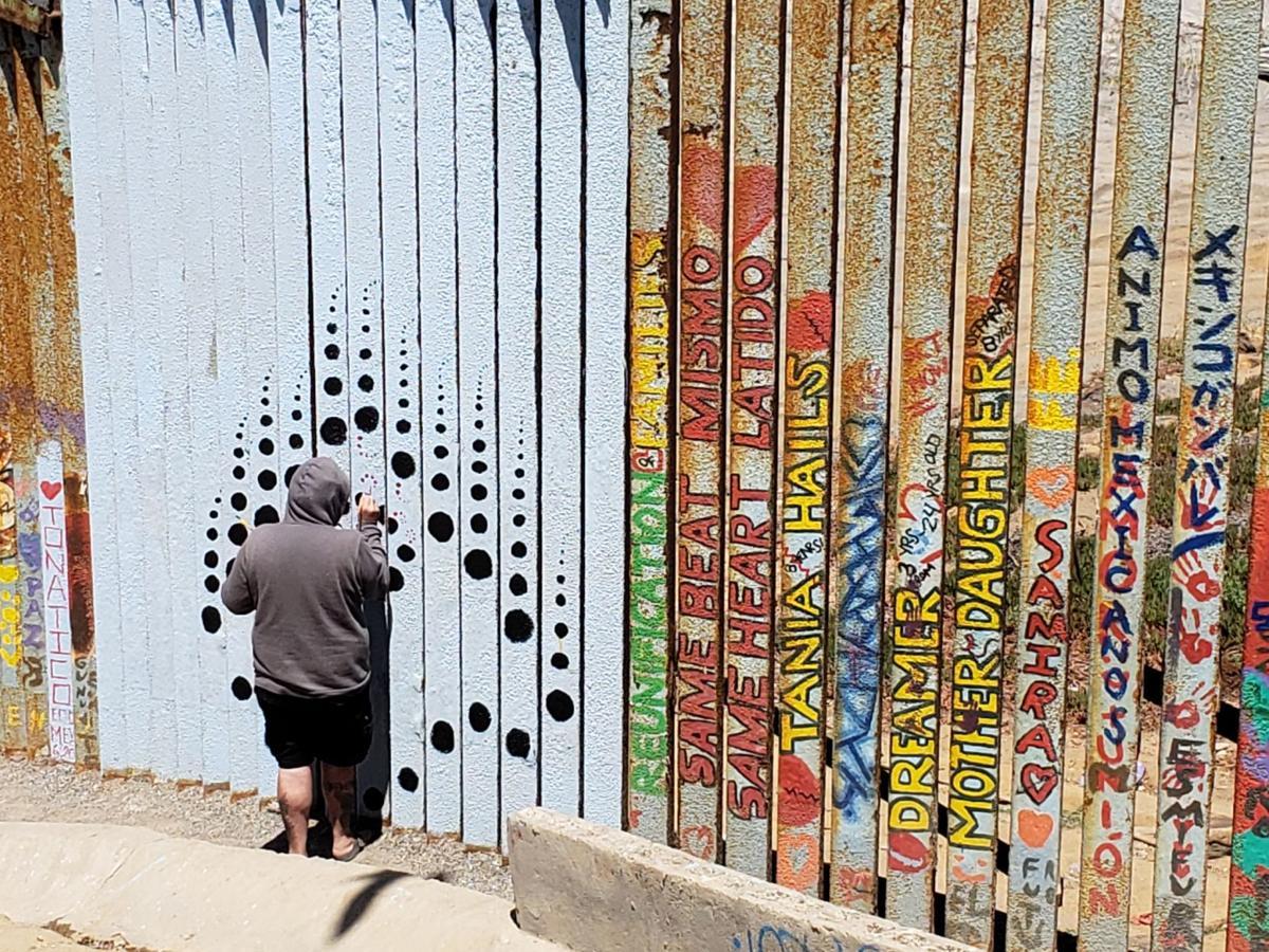 Norman Sotolongo painting border fence