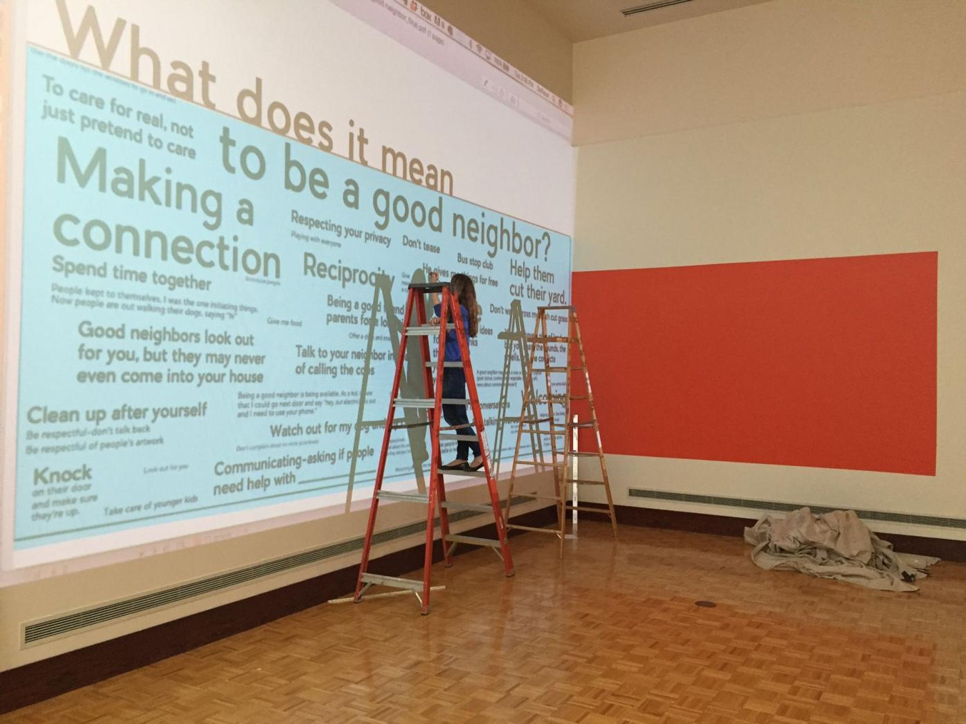 Laura Holzman installing What Does It Mean To Be A Good Neighbor, the House Life Project's contribution to an exhibition on social practice art at UIndy, October 2017. Photo courtesy of Laura Holzman.