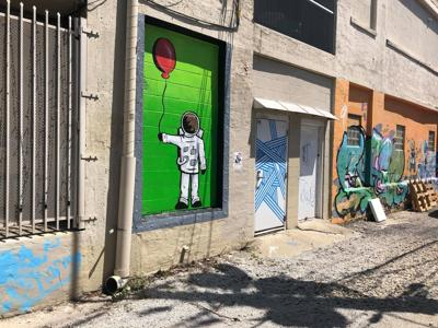 A landlord paints over an alley full of murals in Fountain Square