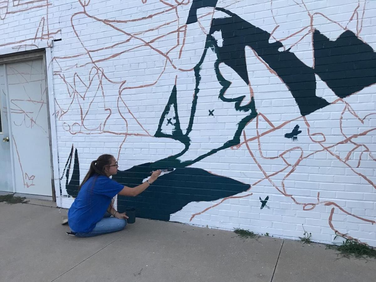 Lydia Hansen helps paint mural in Alton