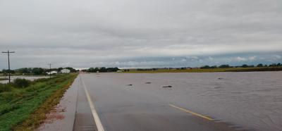 Floodwaters flow over Highway 18
