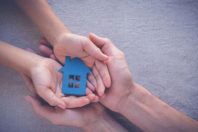 small & big white hands holding cut out house.jpg
