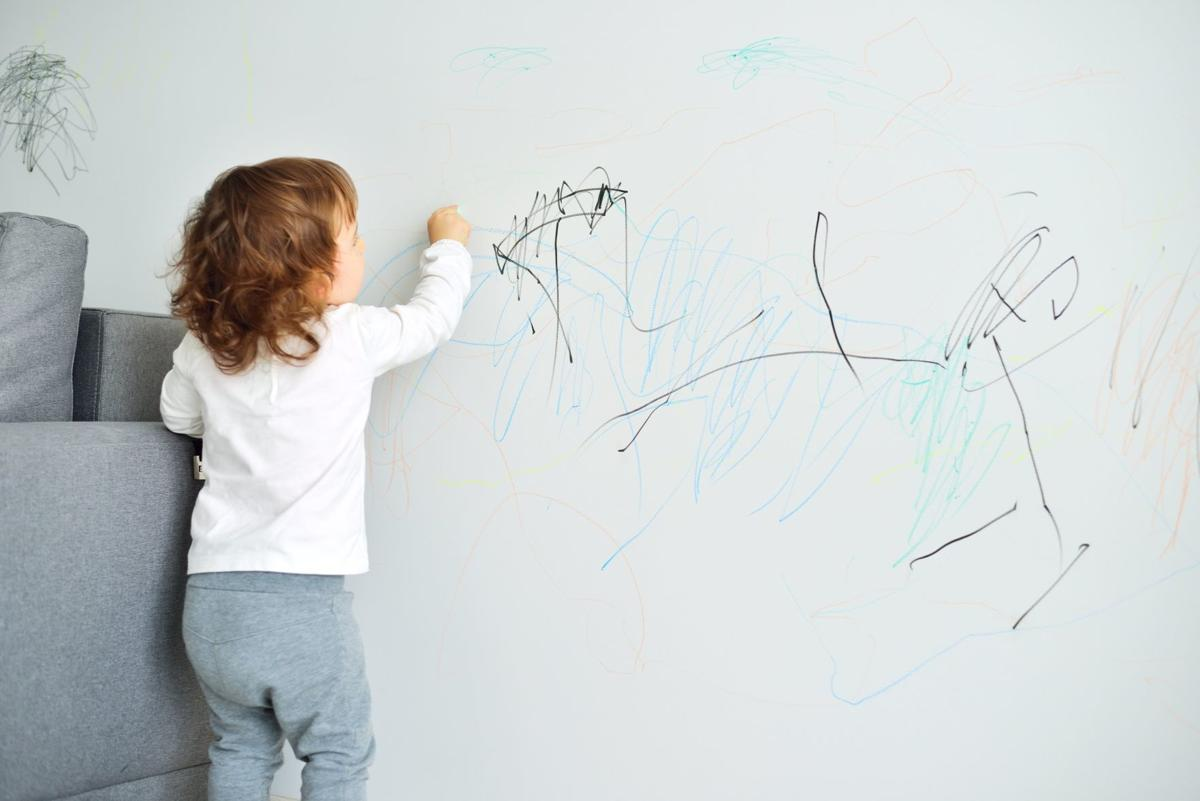 Curly cute little baby girl drawing with crayon color on the wal