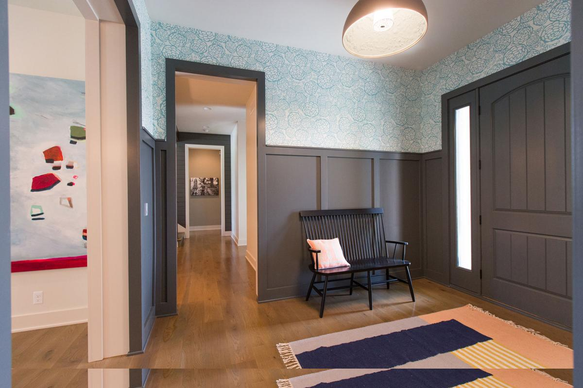 """""""I knew I wanted a defined entry space,"""" says this Omaha homeowner. """"The paneling gives it a sense of formality."""" She found the bench from Schoolhouse Electric and the lighting fixture from Dwell."""