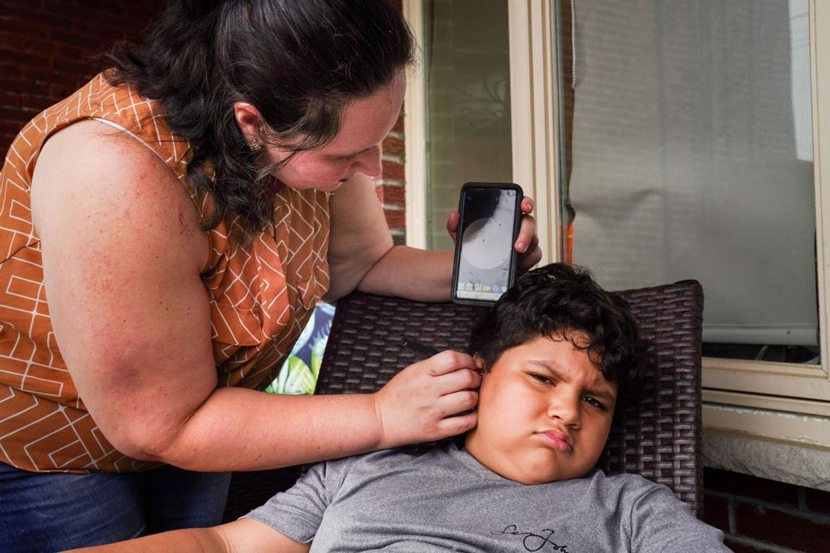 Georgina Rupnarine, left, demonstrates an app and camera that she uses to view the inside of her son Ryan's ear and ear tubes, saying that the device is very helpful for cleaning the ears, in Philadelphia.