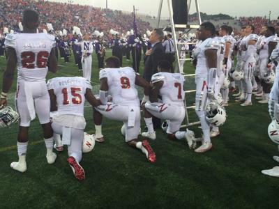 Huskers DaiShon Neal,  Michael Rose-Ivey, Mohamed Barry kneel during national anthem