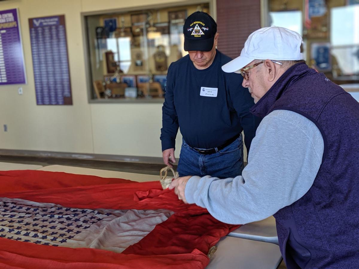 Gene Pfeifer and Harold Pharoah fold flag