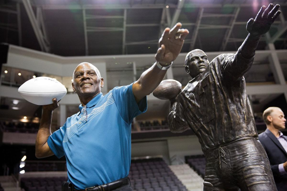 Marlin Briscoe poses with a statue in his likeness