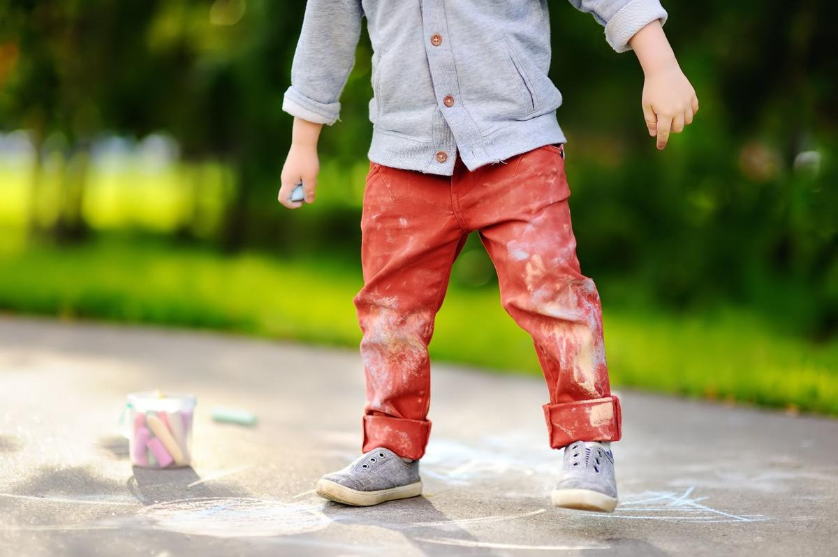 Close-up photo of little kid boy drawing with colored chalk on a