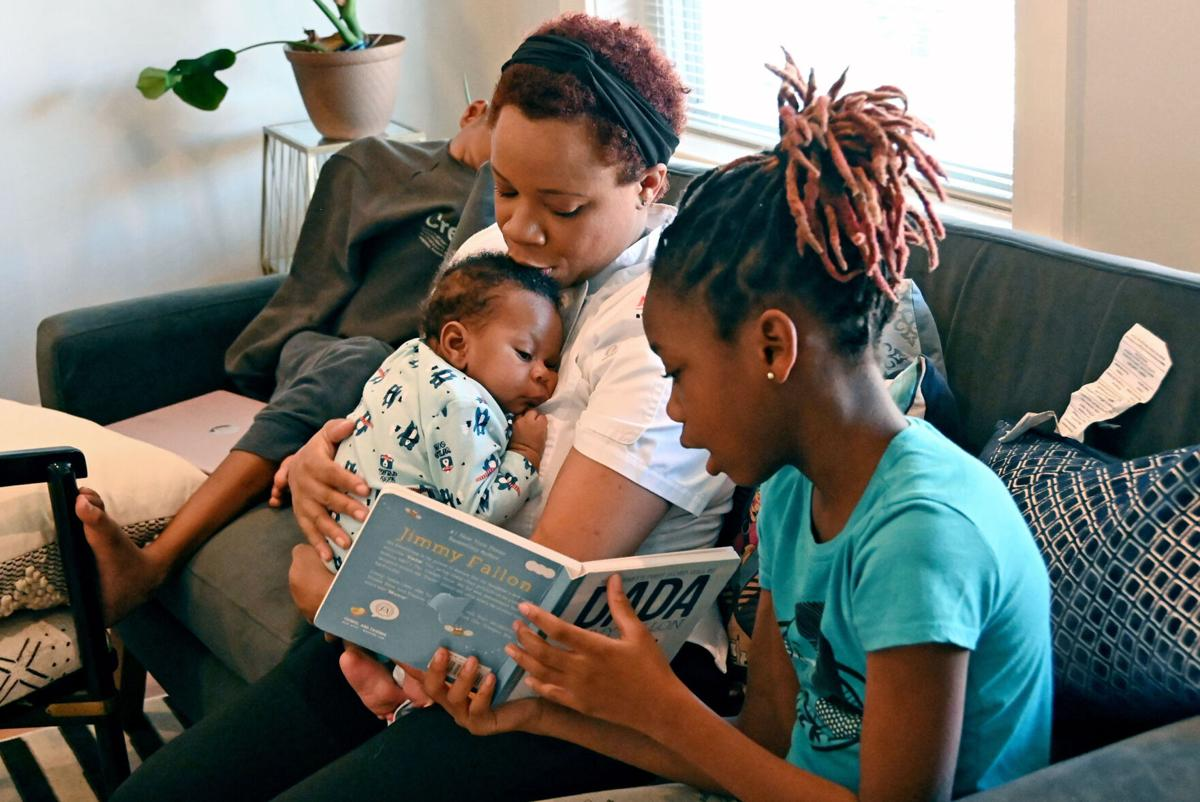 Catina Smith, a personal chef, holds her infant son, Joshua, 2 months, as daughter, Micah, 11, reads to them and son, Isaiah, 12, rests.