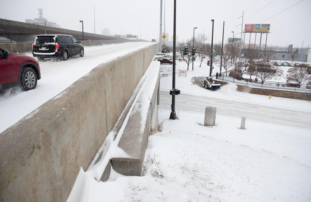 Vehicles make their way on to I-480 as snow is cleared from a sidewalk below on Friday in downtown Omaha.