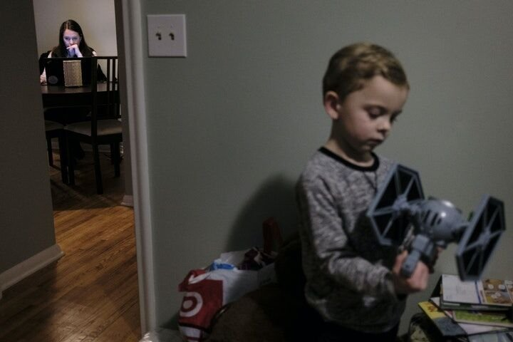 Elena Williams worked on some MCTC school work as her son, Parker, 4, plaid with a Star Wars toy in his room.