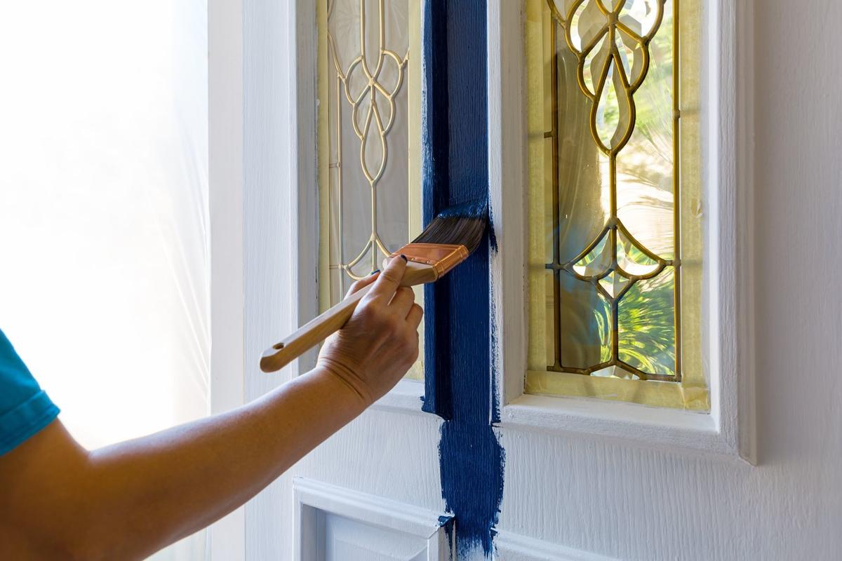 Female Hand holding paint brush Painting House Front Door