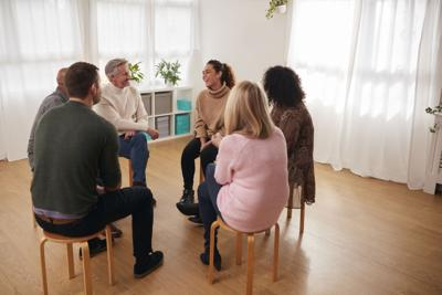 Woman Speaking At Support Group Meeting For Mental Health Or Dependency Issues In Community Space