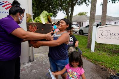 Lorena Sanchez, 23, from Guatemala, picks up fruits and vegetables Thursday, September 16, 2021 during a twice-monthly visit to Wimauma by the Veggie Van, a mobile marketplace operated by the Tampa Metropolitan Area YMCA.