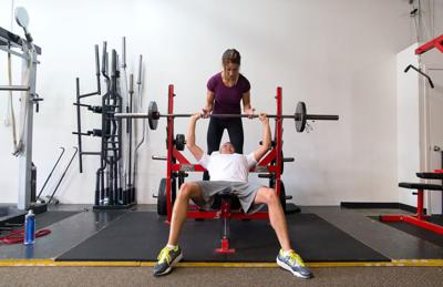 personal trainer helps man work out