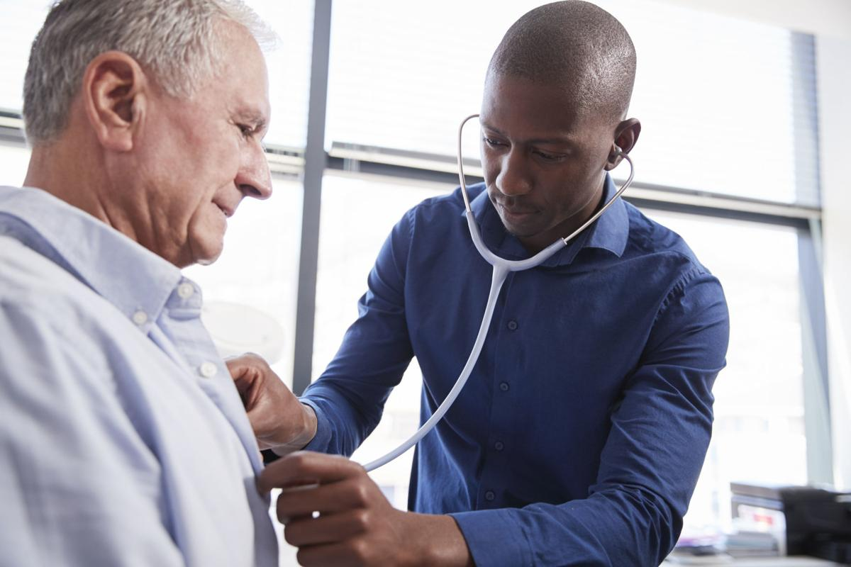 Doctor Listening To Chest Of Senior Male Patient During Medical Exam In Office