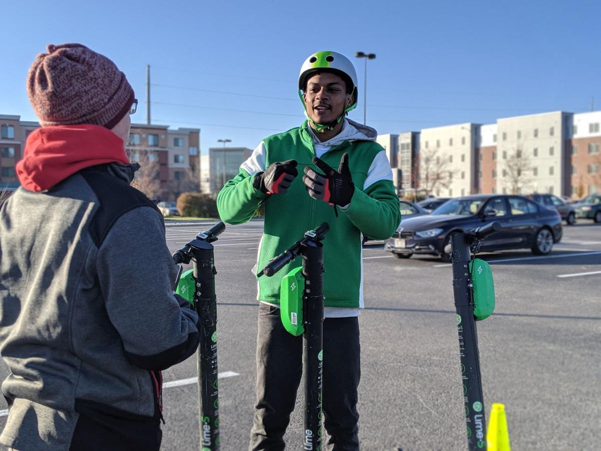 Lime lead operation specialist Jakahi Gregory teaches college student how to ride a scooter