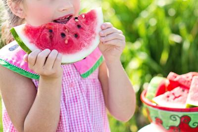 Girl eating watermelon during summer