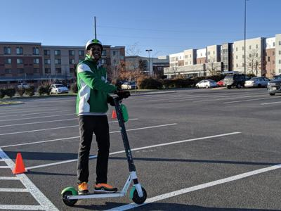 Lime lead operation specialist Jakahi Gregory rides scooter (copy)
