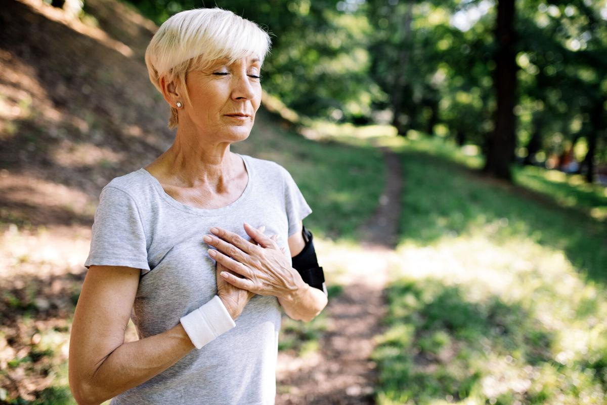 Senior woman with chest pain suffering from heart attack during jogging