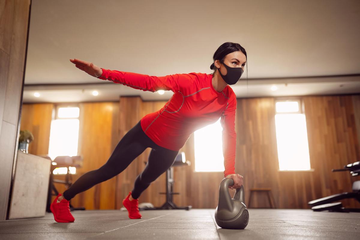 Sport Girl In Mask from Coronavirus doing Kettlebells Planking