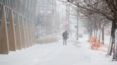 A pedestrian walks into wind blown snow on Friday in downtown Omaha