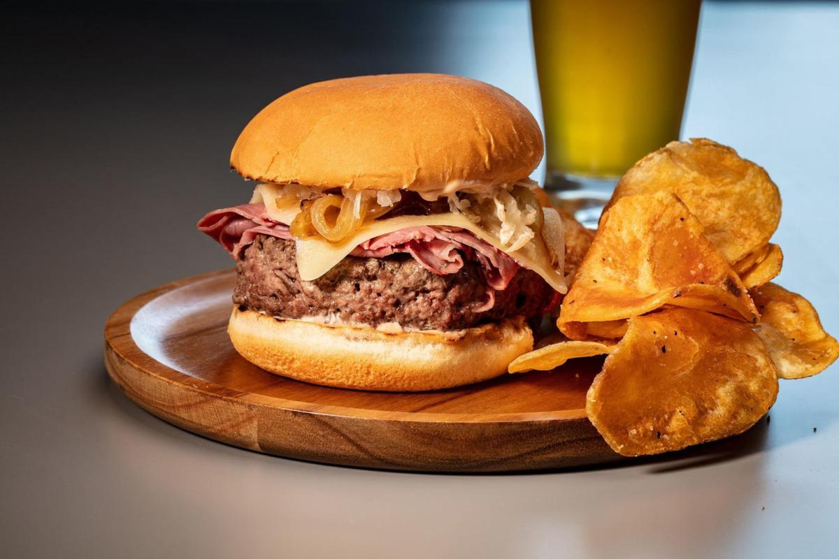 A cheeseburger-corned beef mashup is topped with onions, cheese, sauerkraut and a homemade dressing reminiscent of Thousand Island.