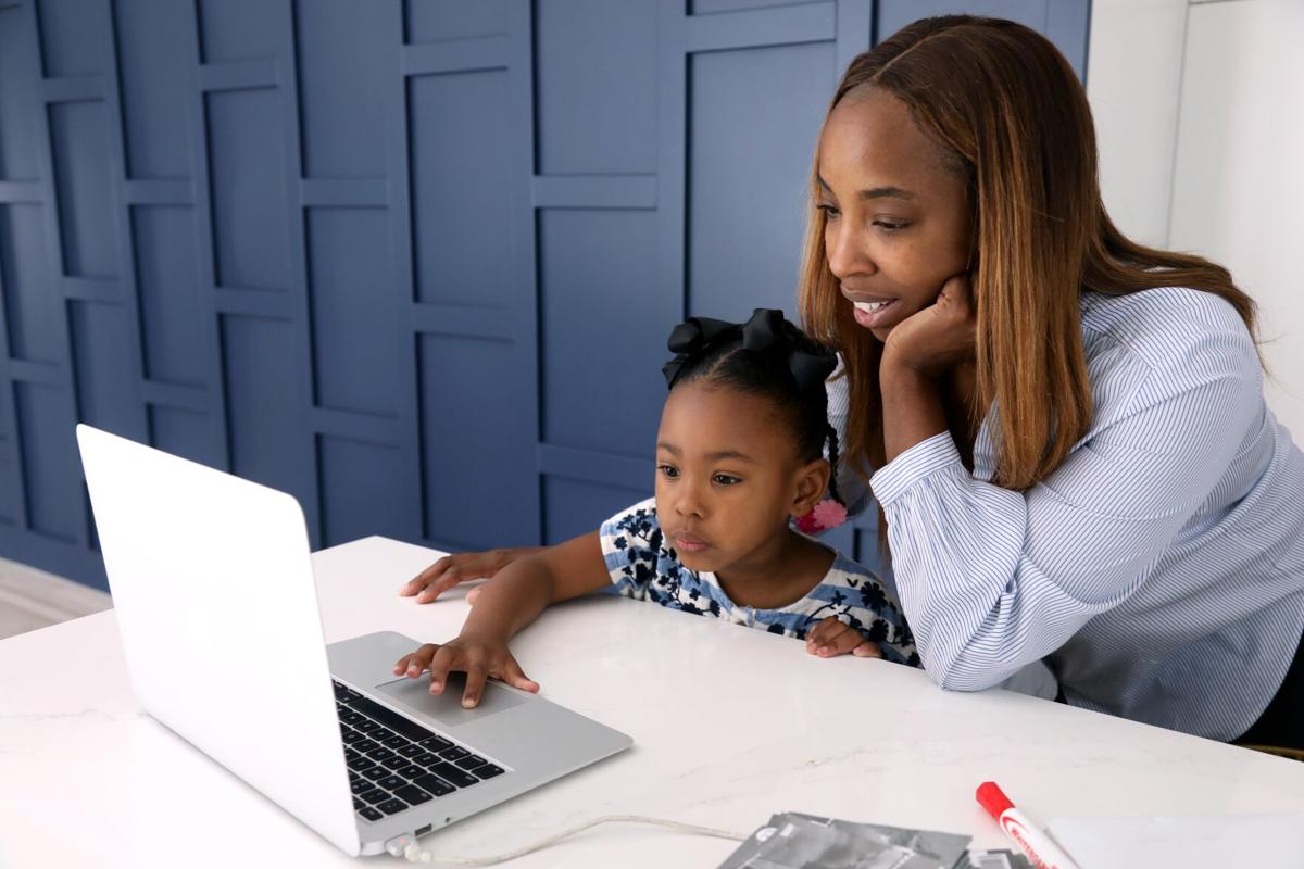 Cali Corbin, 5, a kindergartner at Westwood Charter School, works on a mathematical exercise under the watchful eye of her mother Renee Bailey in their home in Los Angeles on April 9.