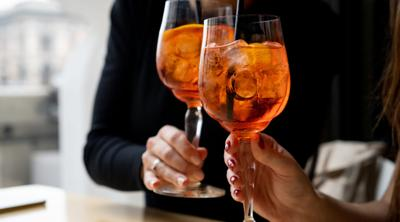 Midsection Of Women Toasting Drinks In Restaurant