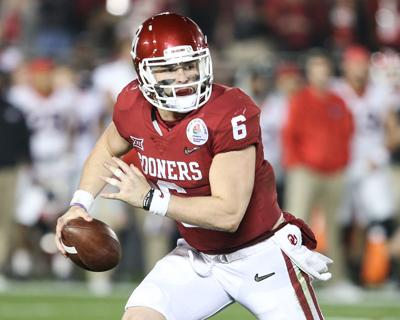 304f84398 Senior quarterback Baker Mayfield runs from the defense during the Rose  Bowl against Georgia Jan. 1. Mayfield signed a deal with the Cleveland  Browns, ...